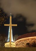 stock photo of olaf  - Tall white cross in front of illuminated tall church and cannon tower in Tallinn Estonia - JPG