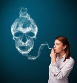 foto of smoking woman  - Pretty young woman smoking dangerous cigarette with toxic skull smoke - JPG