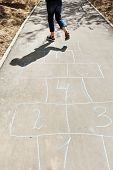 stock photo of hopscotch  - girl hops in hopscotch on urban alley in sunny day - JPG