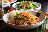 stock photo of gourmet food  - Chicken pad Thai with a variety of other fine Thai food dishes - JPG