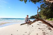 stock photo of glorious  - Teen boy sitting on a gum tree outstretched branch enjoying a vacation on a glorious day at the beach in NSW Australia - JPG