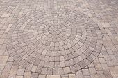 image of paving  - Architectural background of an ornamental pattern in outdoor patio paving with bricks arranged in a circular pattern of concentric geometric circles - JPG