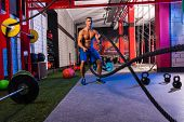 stock photo of battle  - battling ropes man at gym workout exercise fitted body - JPG