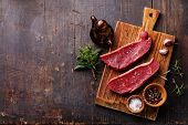 stock photo of meats  - Raw fresh meat Striploin steak and seasoning on dark wooden background - JPG