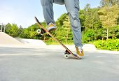 stock photo of skateboarding  - woman skateboarder legs skateboarding at skate park - JPG