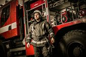 image of firefighter  - Cheerful firefighter near truck with equipment  - JPG