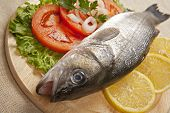 picture of bass fish  - Freshly Bass Fish with vegetables on wooden cutting board - JPG