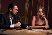 image of competing  - Handsome  man and beautiful woman in casino competing looking at each other holding in hands chips and cards sitting at table - JPG