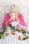 picture of pyjama  - Sad woman in pink pyjama sitting in bed with a bunch of roses and tissues - JPG