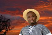 image of mans-best-friend  - Outdoor portrait of a South African black man with friendly smiling facial expression on a red sky sunrise background. ** Note: Visible grain at 100%, best at smaller sizes - JPG