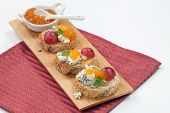 foto of apricot  - Blue cheese and apricot jam multigrain crostini with grapes and parsley on wooden tray - JPG
