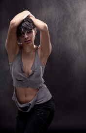 stock photo of strip tease  - Wet young woman with a torn shirt  Fine spray of water - JPG