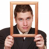 foto of dork  - Nerdy funny business man guy framing his face with wooden empty picture frame isolated on white background - JPG