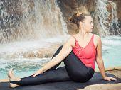 pic of twist  - Woman practicing yoga near waterfall - JPG
