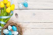 stock photo of egg whites  - Easter background with blue and white eggs in nest and yellow tulips - JPG
