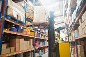 picture of forklift driver  - Focused driver operating forklift machine in warehouse - JPG