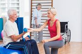 pic of senior class  - Female trainer assisting senior man in exercising with dumbbells while woman using crutches in background at gym - JPG
