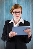 stock photo of redhead  - Redhead businesswoman using her tablet pc against wooden planks - JPG
