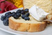 picture of pound cake  - Slice of pound cake with whipped cream topped and blueberries with flowers in the background - JPG
