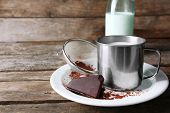 stock photo of bittersweet  - Metal mug and glass bottle of milk with chocolate chunks and strainer of cocoa on plate and rustic wooden planks background - JPG