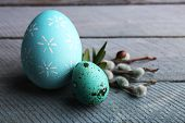 image of pussy-willows  - Bird colorful eggs in nest and pussy willow branches on wooden background - JPG