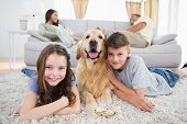 stock photo of lie  - Portrait of happy siblings lying with dog while parents resting on sofa at home - JPG