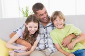 image of tickle  - Happy father tickling children while sitting on sofa at home - JPG