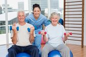 foto of senior class  - Portrait of happy female instructor with arms around senior couple in gym - JPG