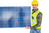 stock photo of handyman  - Handyman in protective clothing carrying solar panel on white background - JPG
