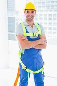 stock photo of harness  - Portrait of happy manual worker wearing safety harness standing arms crossed in bright office - JPG