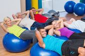 stock photo of bending over backwards  - Portrait of happy people stretching on exercise balls in fitness club - JPG