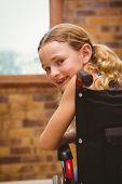 foto of wheelchair  - Portrait of cute little girl sitting in wheelchair in school - JPG