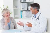 pic of senior adult  - Happy male doctor discussing with senior patient at table in clinic - JPG