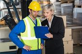 foto of forklift driver  - Forklift driver talking with his manager in a large warehouse - JPG