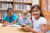 pic of pupils  - Cute pupil using tablet computer in library at the elementary school - JPG
