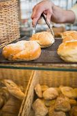 picture of tong  - Hand of waiter taking bread with tongs at the bakery - JPG