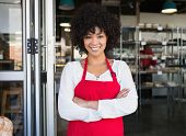 picture of apron  - Pretty server in red apron with arms crossed at the bakery - JPG