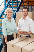image of warehouse  - Smiling warehouse managers with clipboard in a large warehouse - JPG