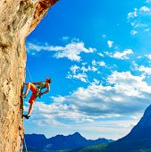 stock photo of rocking  - female rock climber climbs on a rocky wall