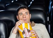 foto of popcorn  - Frightened man eating popcorn while watching movie in cinema theater - JPG
