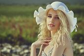 stock photo of natural blonde  - Portrait of a gorgeous young lady with long blond curly hair wearing white sun hat over blurred natural background - JPG