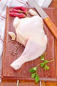 picture of gobbler  - raw chicken leg with pepper on the wooden board - JPG