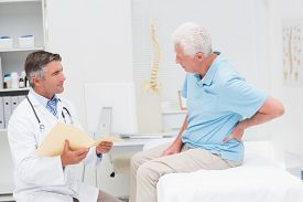 picture of suffering  - Male doctor discussing reports with senior patient suffering from back pain in clinic - JPG