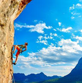 stock photo of rocking  - female rock climber climbs on a rocky wall  - JPG