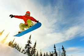 image of winter sport  - Snowboarder jumping through air with deep blue sky in background - JPG