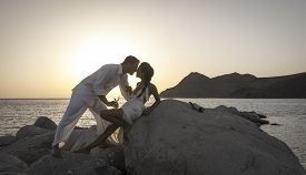 stock photo of bareback  - Silhouette of young attractive couple at sunrise on beach rocks - JPG