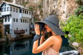 picture of cave woman  - Young woman in pink dress and hat photographing house in Blagaj village in Bosnia and Herzegovina - JPG
