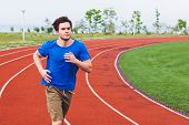 Постер, плакат: Young fit male in blue shirt running on a stadium running path