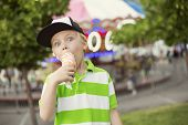 picture of carnival ride  - Cute boy fully enjoying an ice cream cone during a summer carnival or fair - JPG