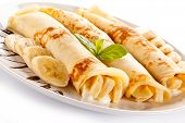 pic of crepes  - Crepes with bananas and cream on white background  - JPG